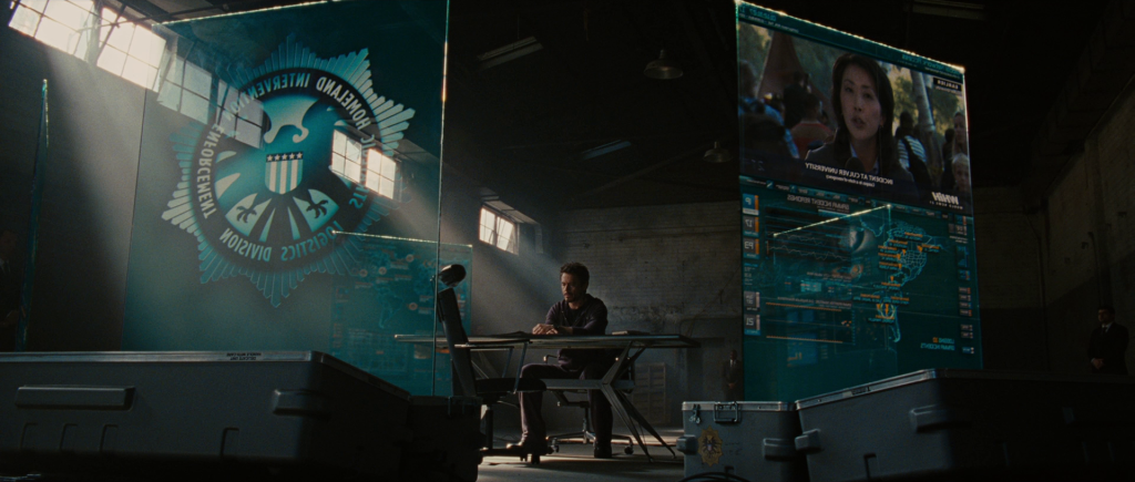 Tony Stark in a warehouse surrounded by S.H.I.E.L.D. information displays.