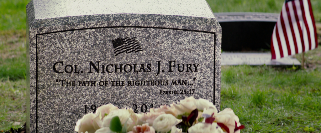 Nick Fury's headstone with years obscured by flowers.