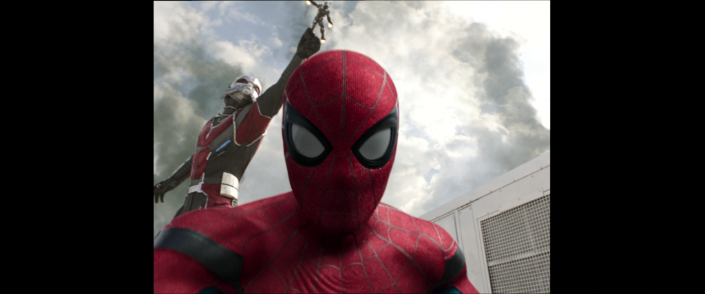 Spider-Man records footage of himself during the battle as Scott Lang turns giant in the background.