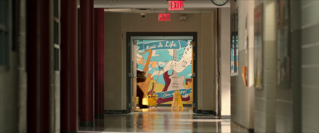 School hallway with a mural at the end. The mural depicts a saxophone, a trumpet, a violin, and an electric, with the phrase